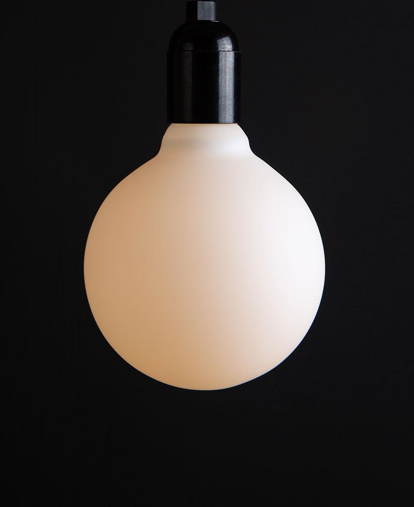 Lit Aurora decorative light bulbs suspended from bakelite bulb holder against black wall