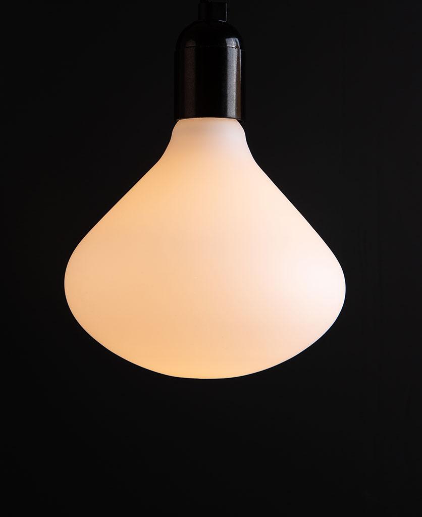 Lit Nova decorative LED light bulb suspended from black bakelite bulb holder against black wall