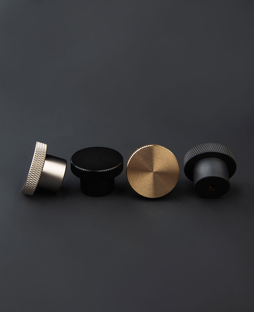 group shot of four modernist chest of drawer handles in silver, black, gold & antique black on dark grey background