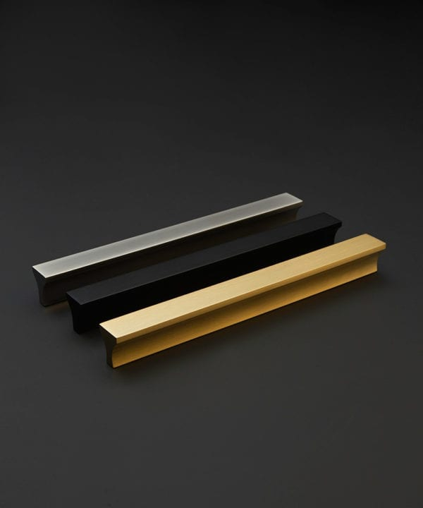 metal kitchen door handle in black gold and silver against a black background