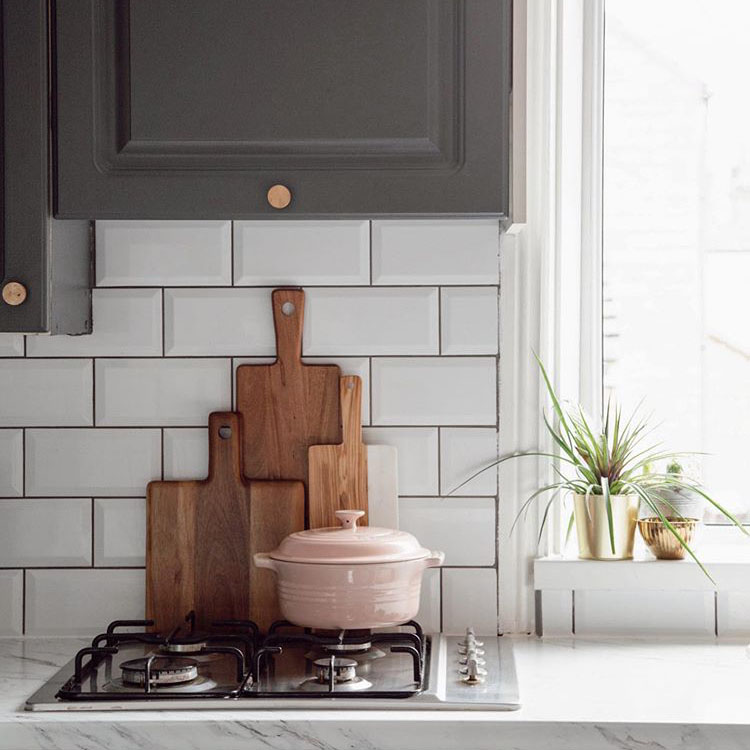 brass modernist large knob on dark grey cupboard in a grey and white kitchen