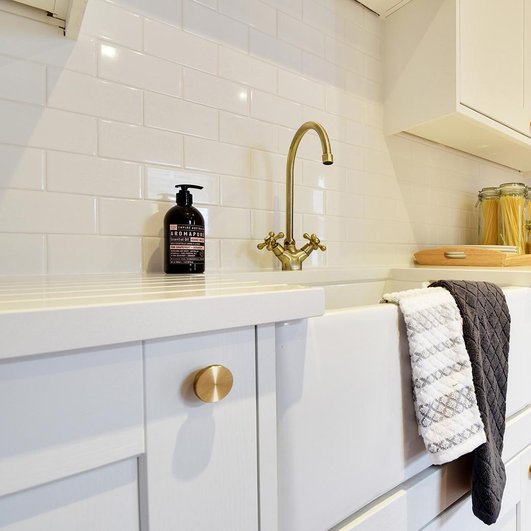 gold modernist drawer knob on a white kitchen cupboard