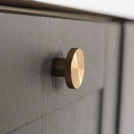 brass modernist large knob on a dark grey cupboard