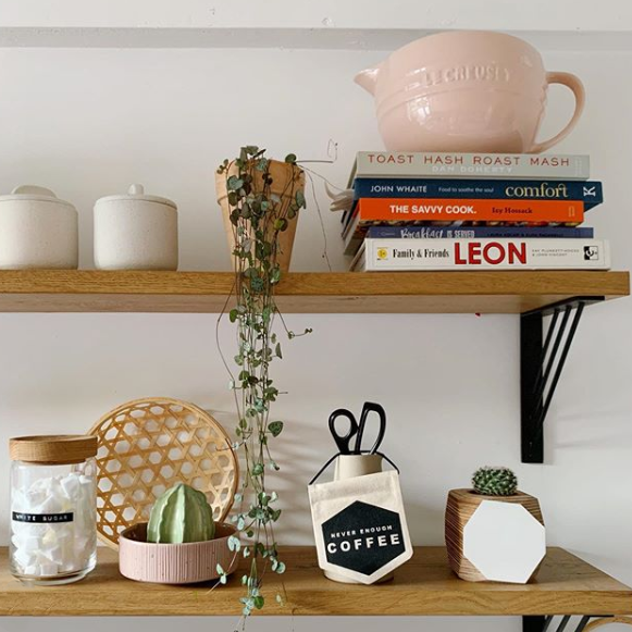 black ingrd shelf brackets holding up wooden shelves with cookbooks, pots and succulents