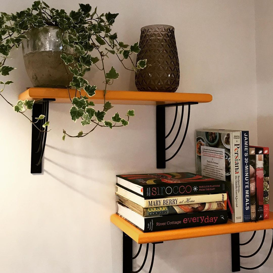 Marylin shelf bracket with wooden shelf holing trailing ivy and a glass vase against a white wall