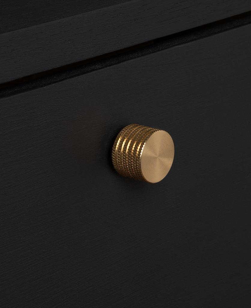 large avant garde gold knob on black drawer