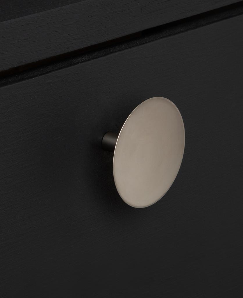 large rococo silver knob on black drawer