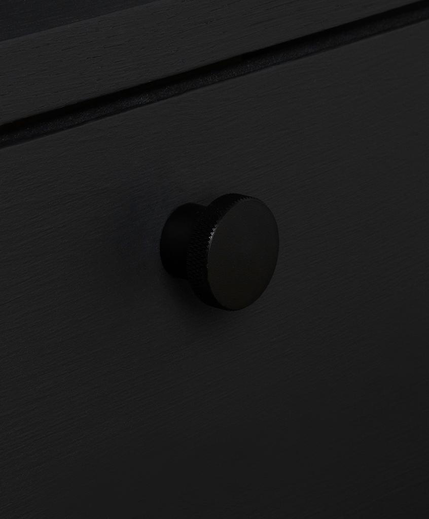 black circular metal kitchen drawer knob on black drawer