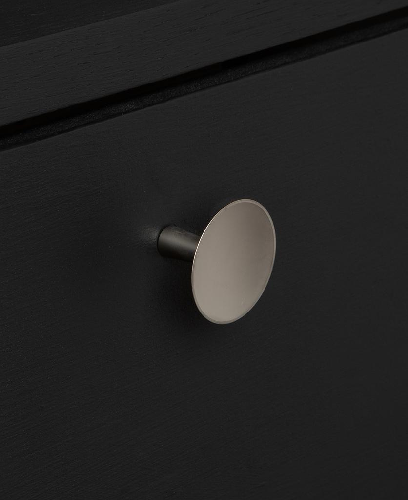 small rococo silver knob on black drawer