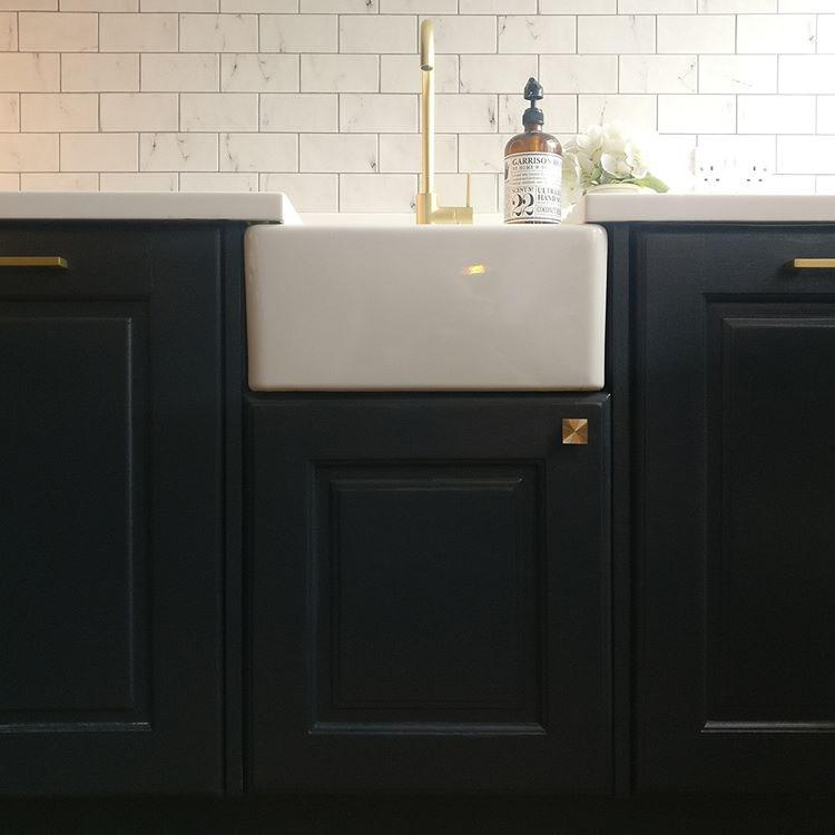 gold expressionist knob on a black under sink cupboard in a monochrome kitchen