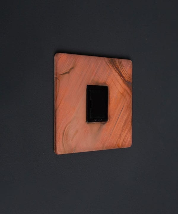 tarnished copper and black unswitched fuse spur against black background