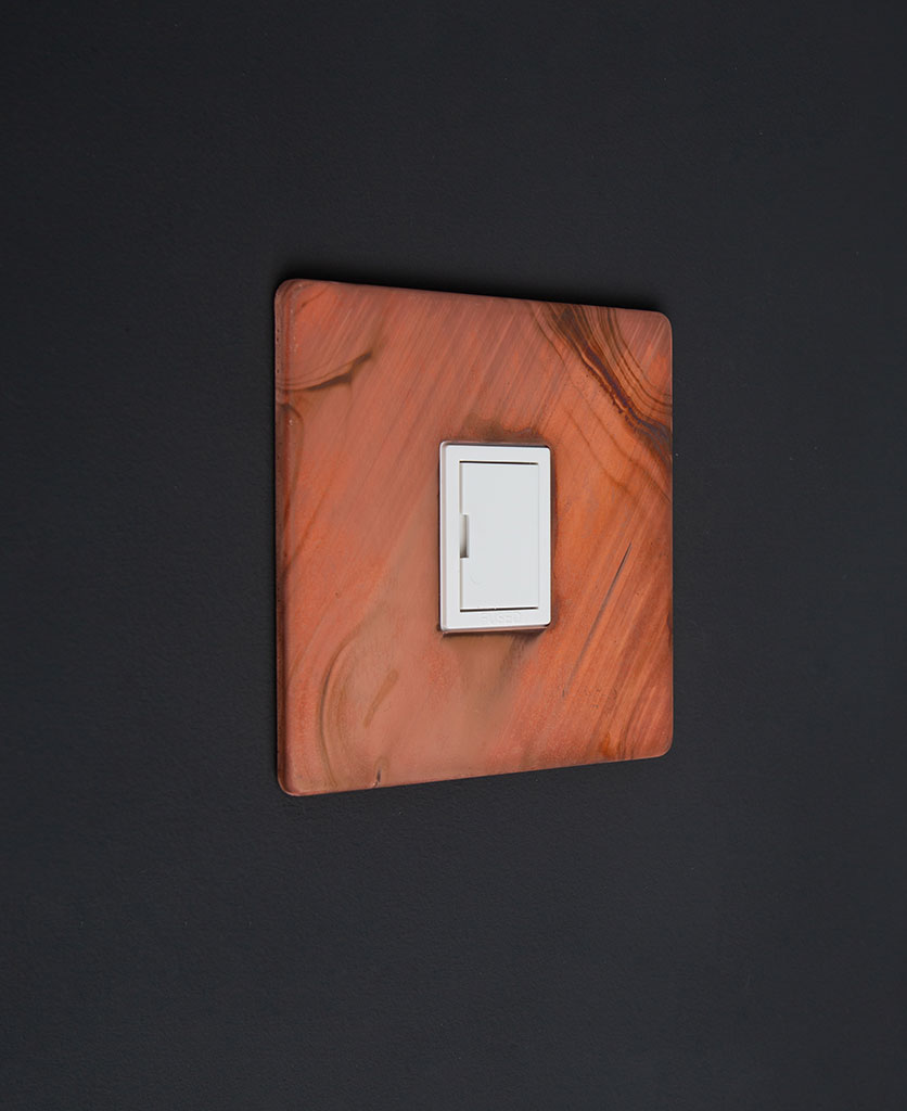 tarnished copper and white unswitched fuse spur against black background