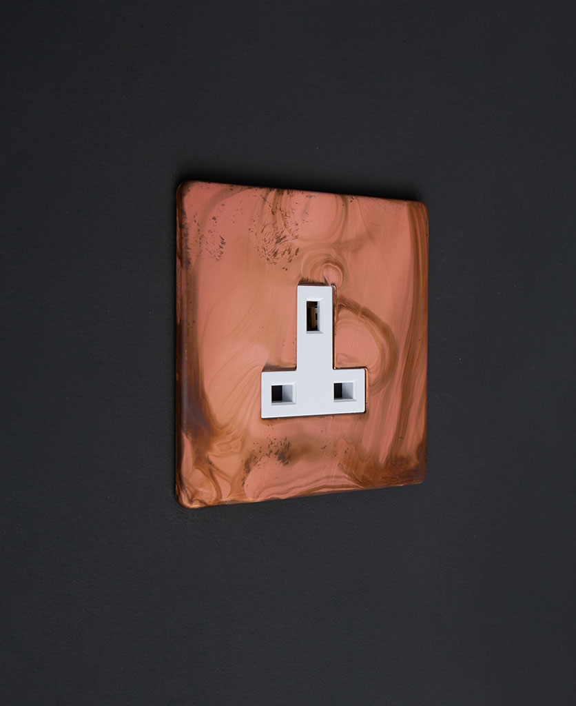 13A unswitched copper sockets tarnished copper socket with white insert against black wall