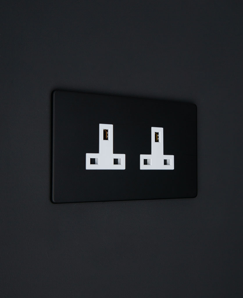 black & white double unswitched socket on a black wall