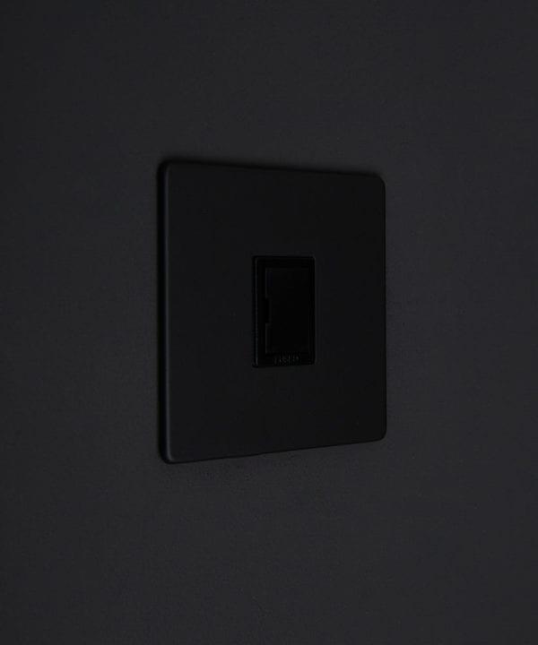 black fused spur switch against black background