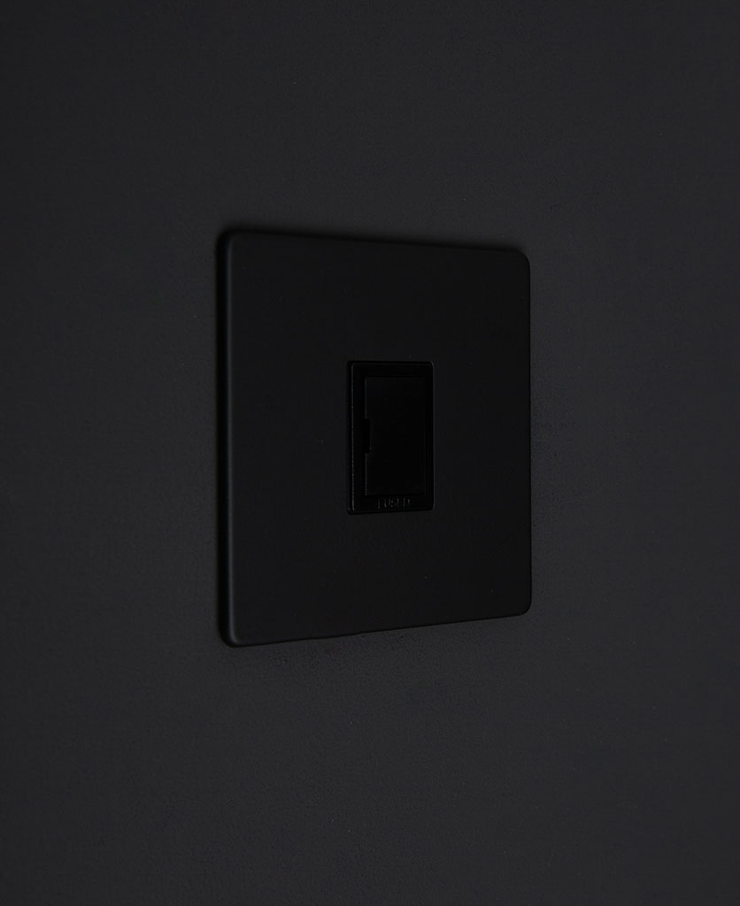 black fused spur switch against black background