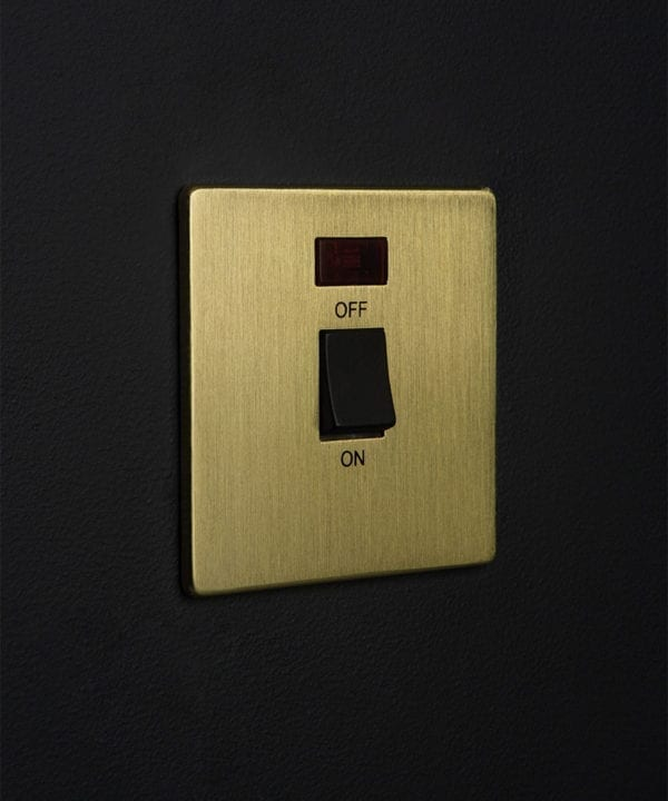 gold and black 20A DP switch against black wall