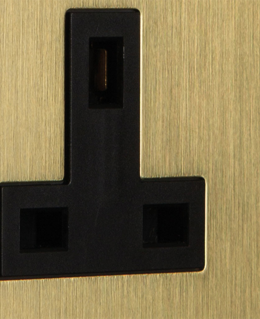 closeup of gold & black unswitched double socket on a black wall
