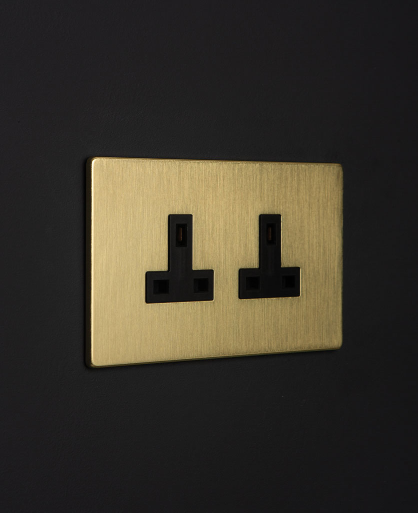 gold plug sockets with black inserts on a black wall
