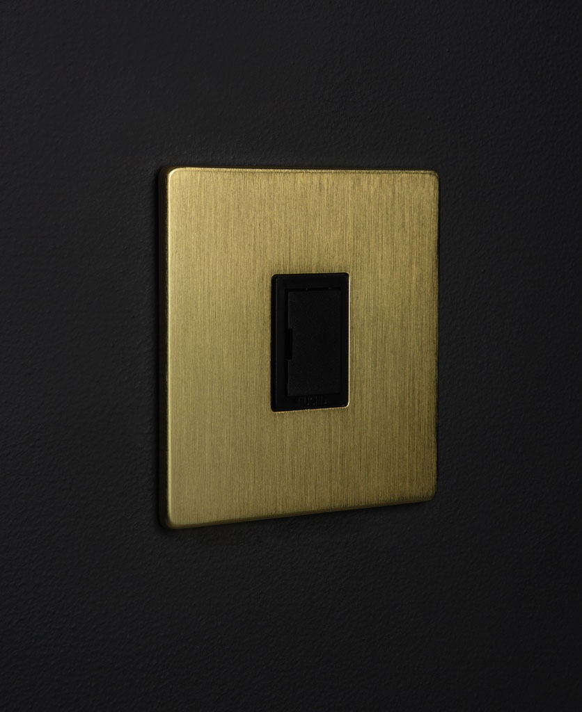 gold and black unswitched fuse spur switch against black background