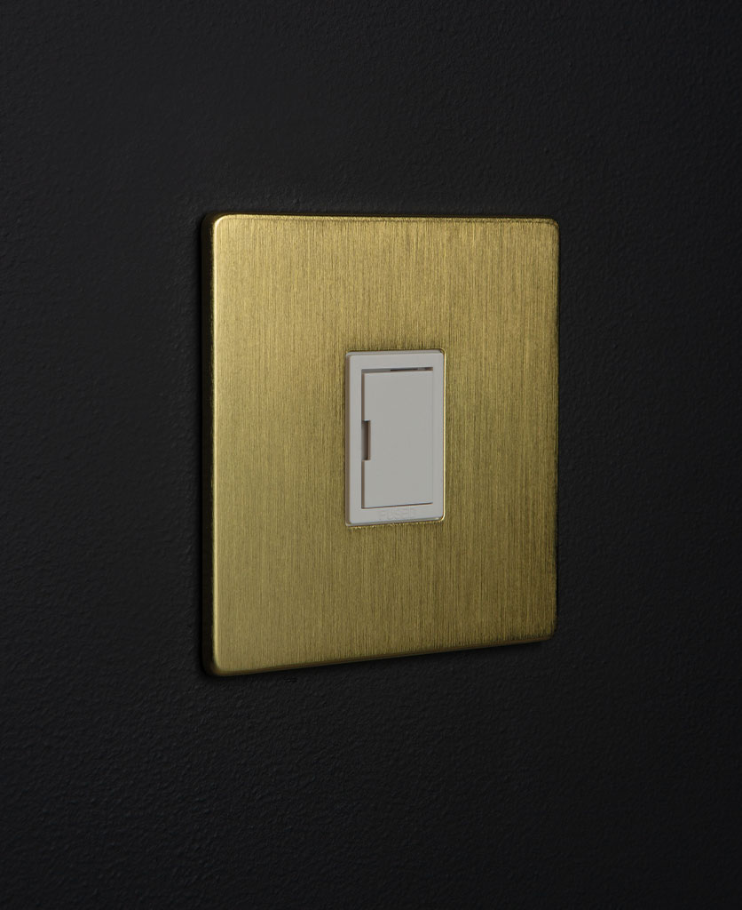 gold and white unswitched fuse spur switch against black background