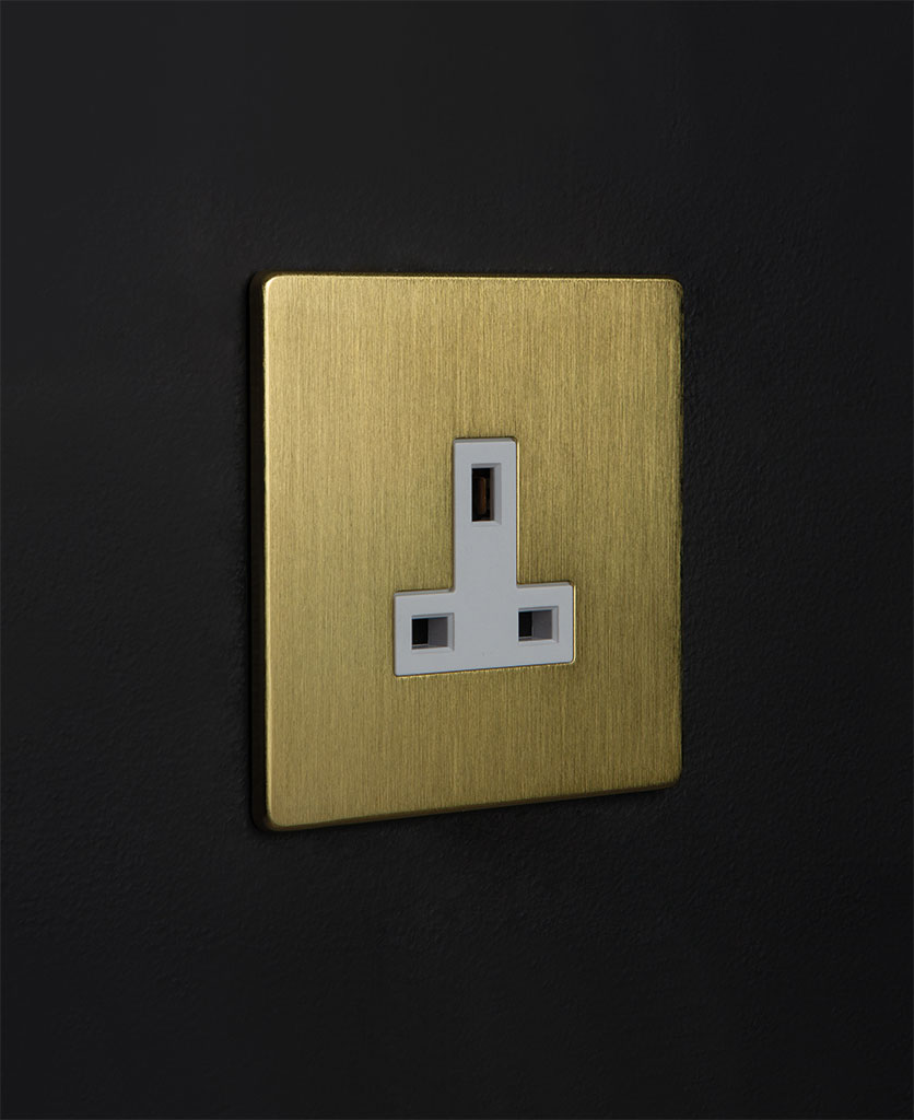 gold unswitched plug socket with white detail against black background