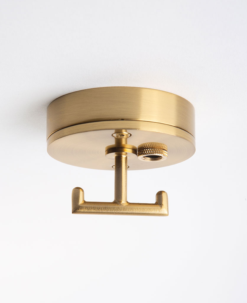 raw brass ceiling rose with t shaped hook against white background