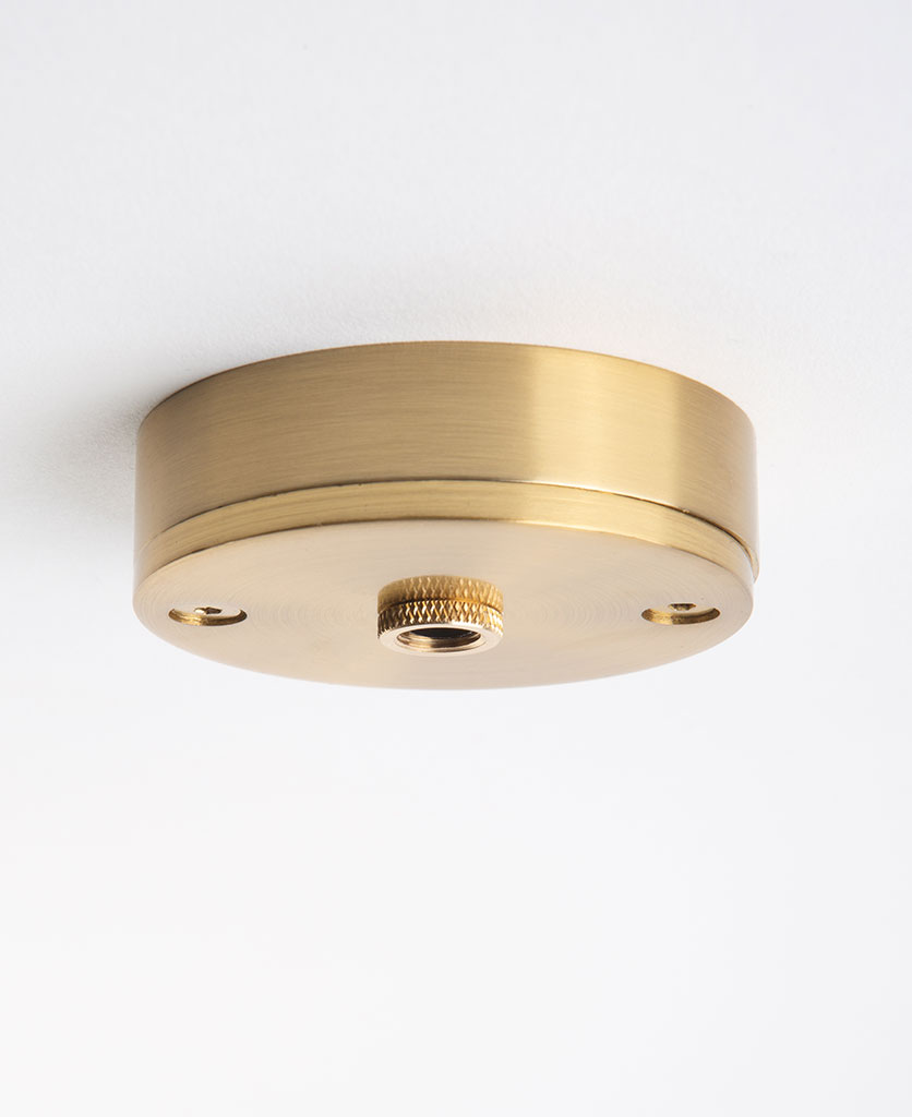 small raw brass ceiling rose against white background