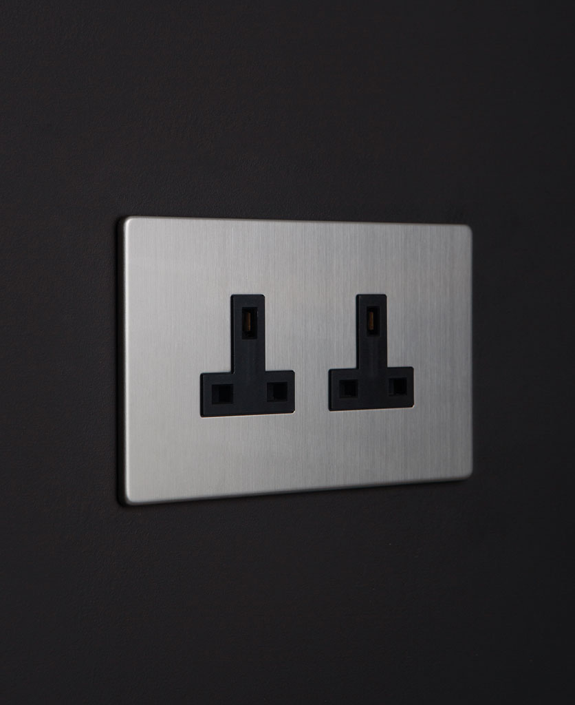 silver plug sockets with black inserts against a black wall