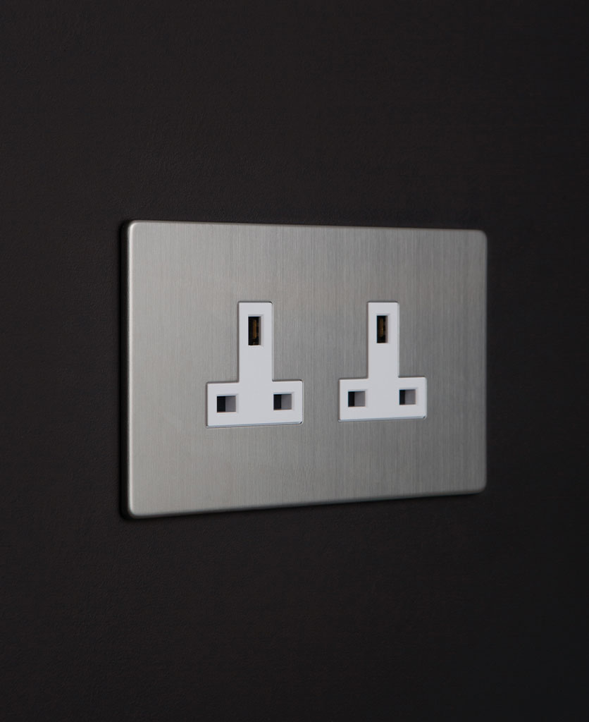 unswitched socket featuring silver plate with white inserts on black wall