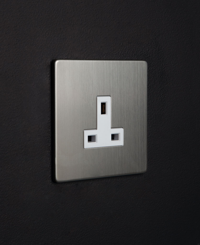 brushed silver sockets with white insert against black wall