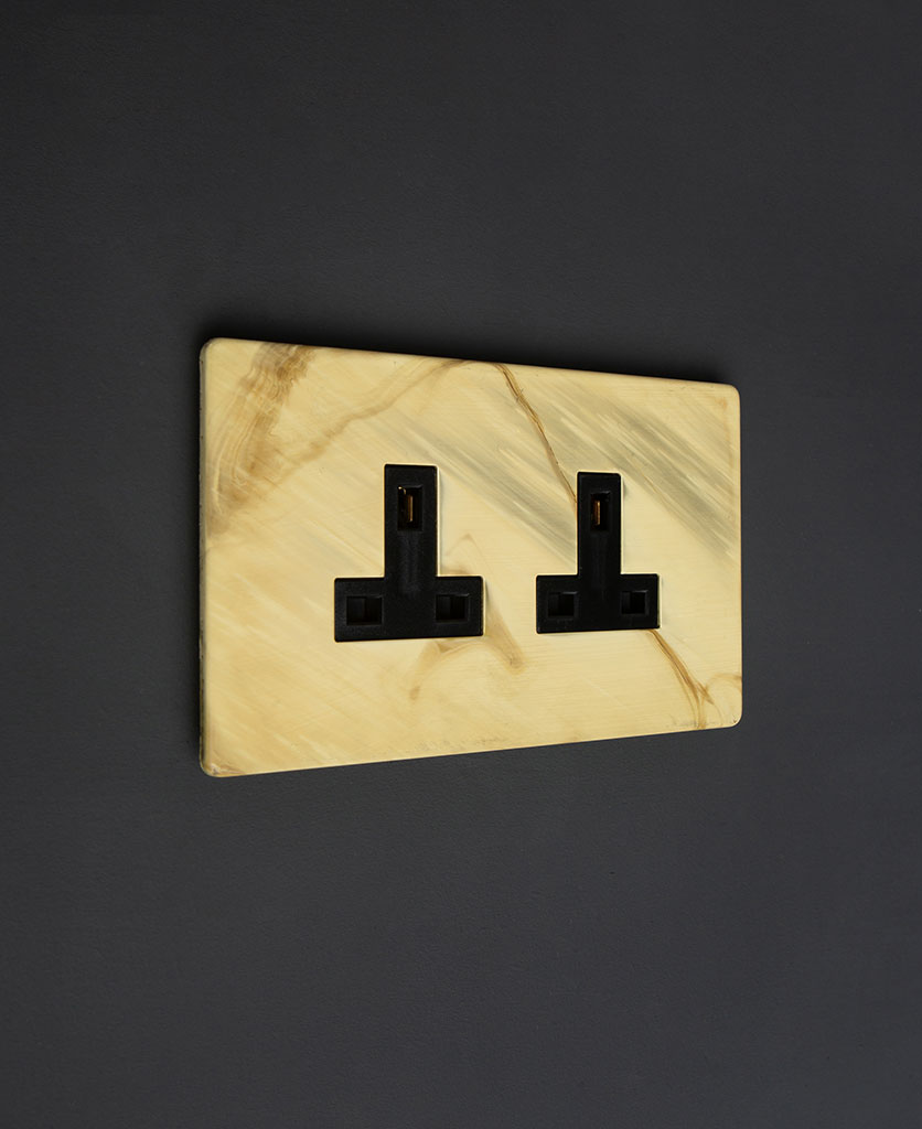 smoked gold & black electric plug sockets against black background