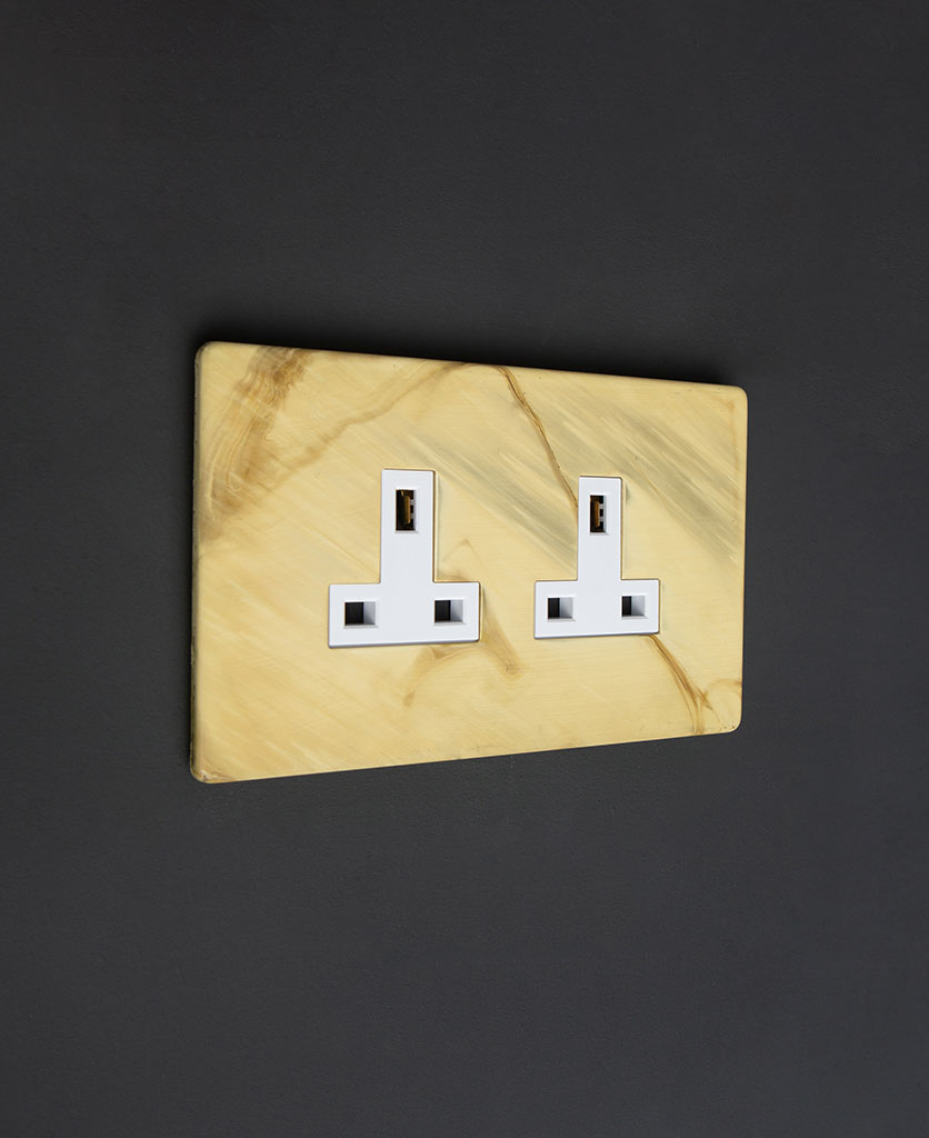 smoked gold & white electric plug sockets against black background