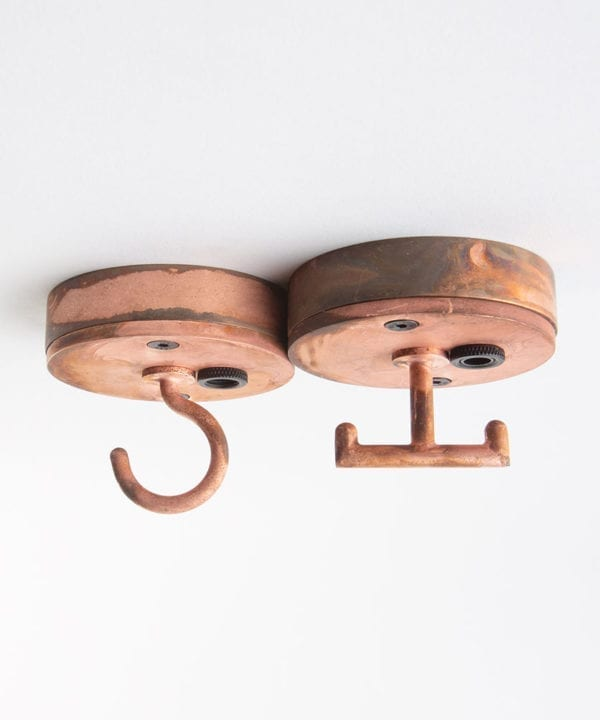 Small copper hooked ceiling rose industrial light fittings against white background