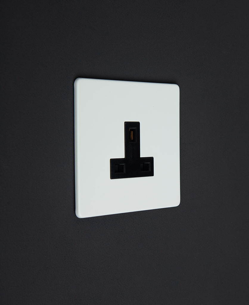 white wall plug socket with black insert against a black wall