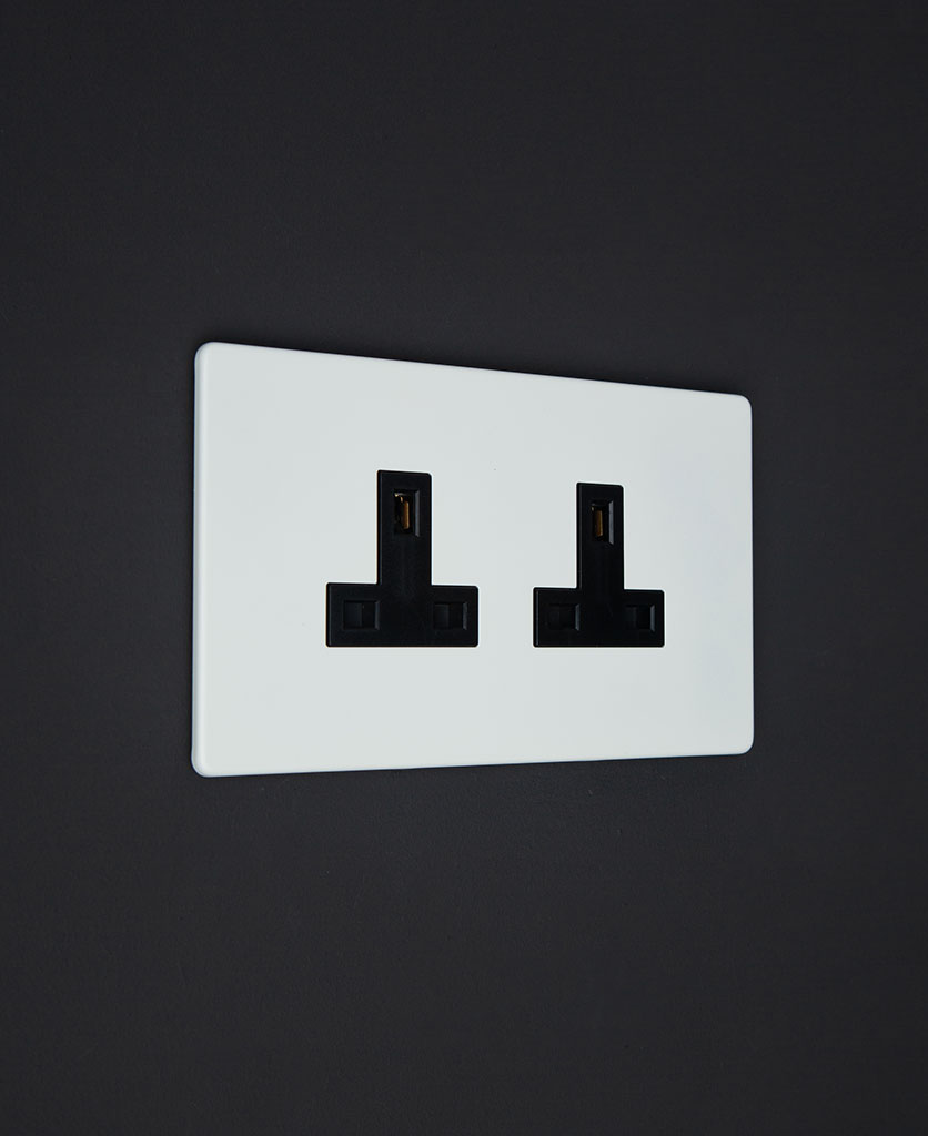 unswitched white double socket with black inserts against a black wall