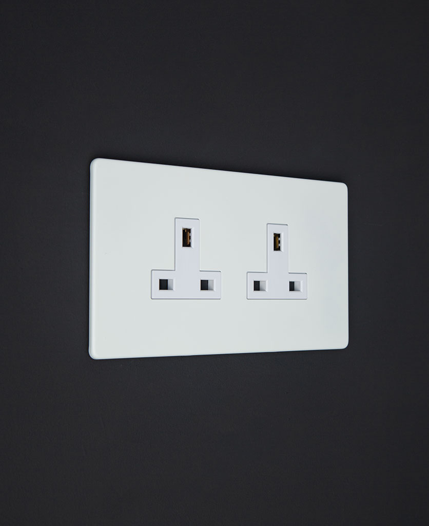 unswitched white double socket with white inserts against a black wall