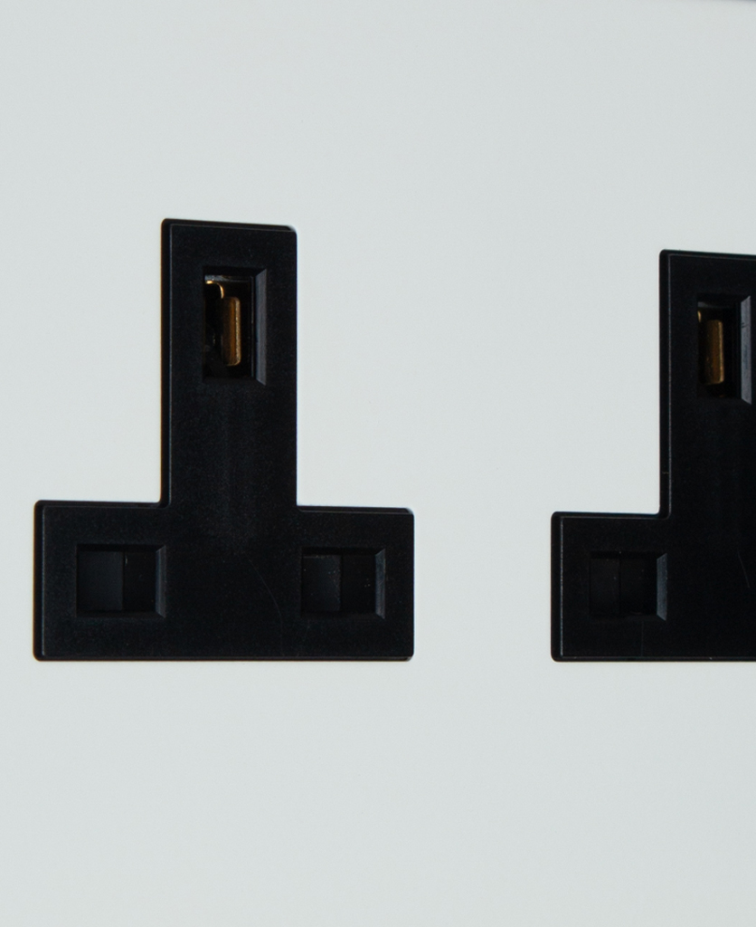 white and black double unswitched plug socket close up