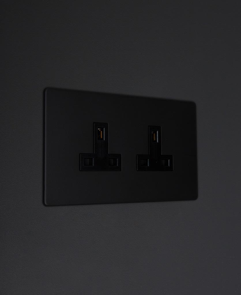 black double unswitched 2g plug socket on black background