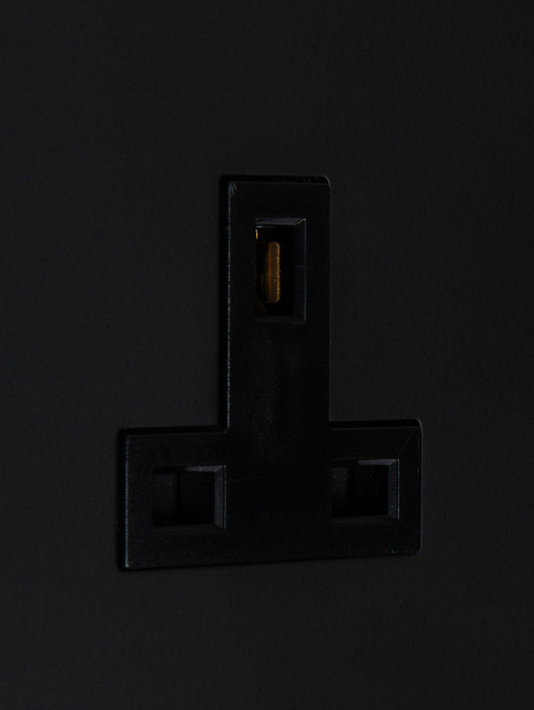 black unswitched single 1g plug socket close up
