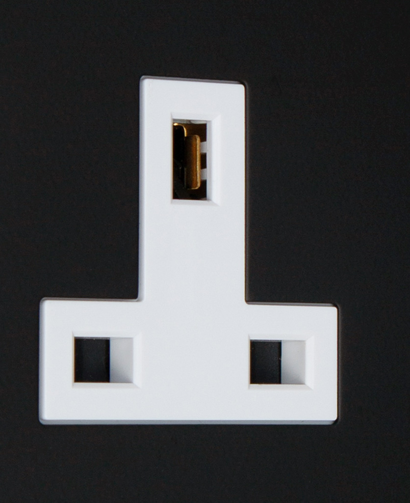 black and white double unswitched 2g plug socket on black background close up