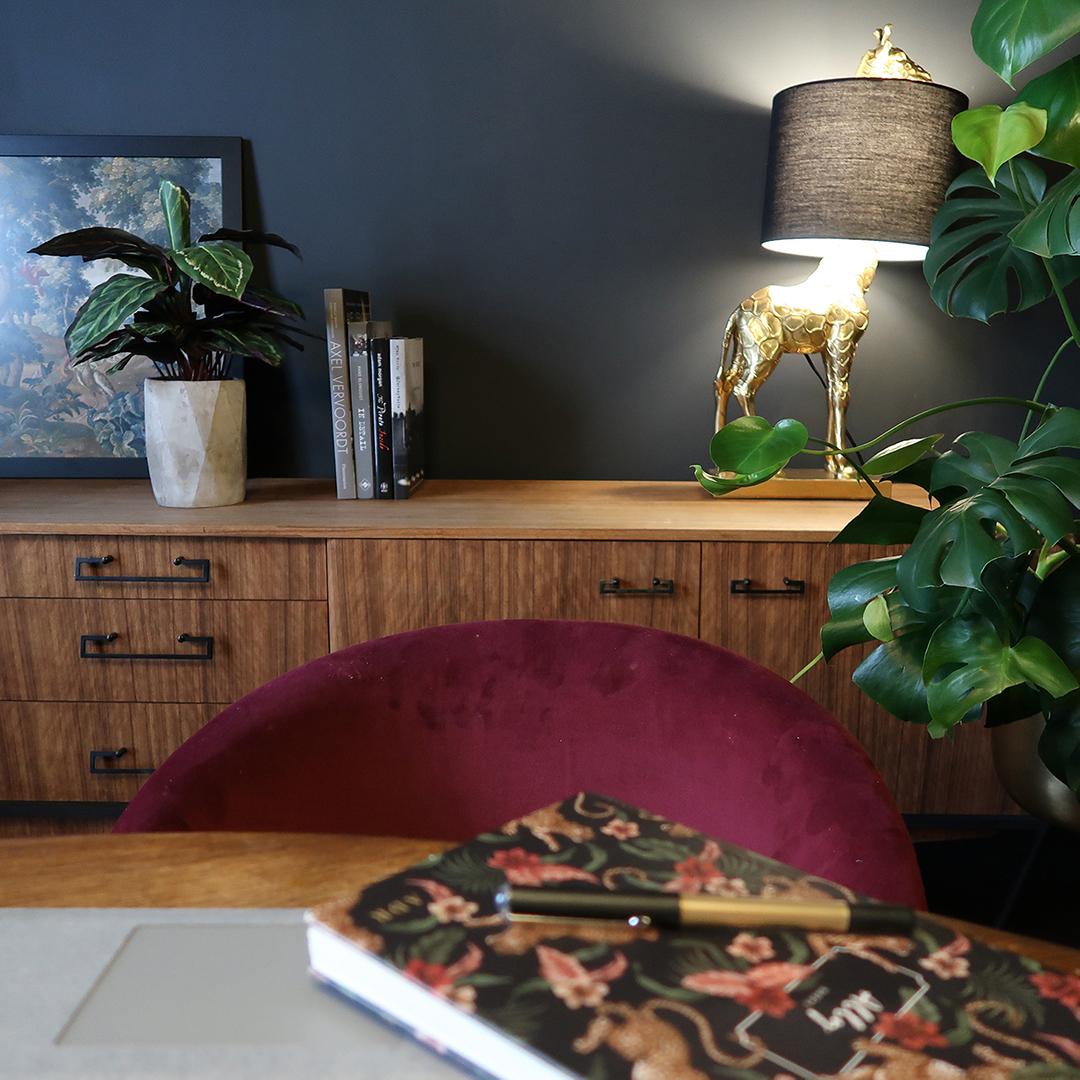 giraffe table lamp sat on wooden unit against black wall