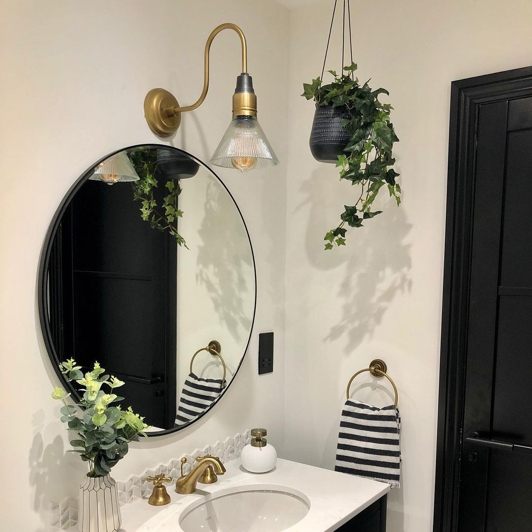 Ivy artificial trailing plant in black pot hanging from the ceiling in a black and white bathroom