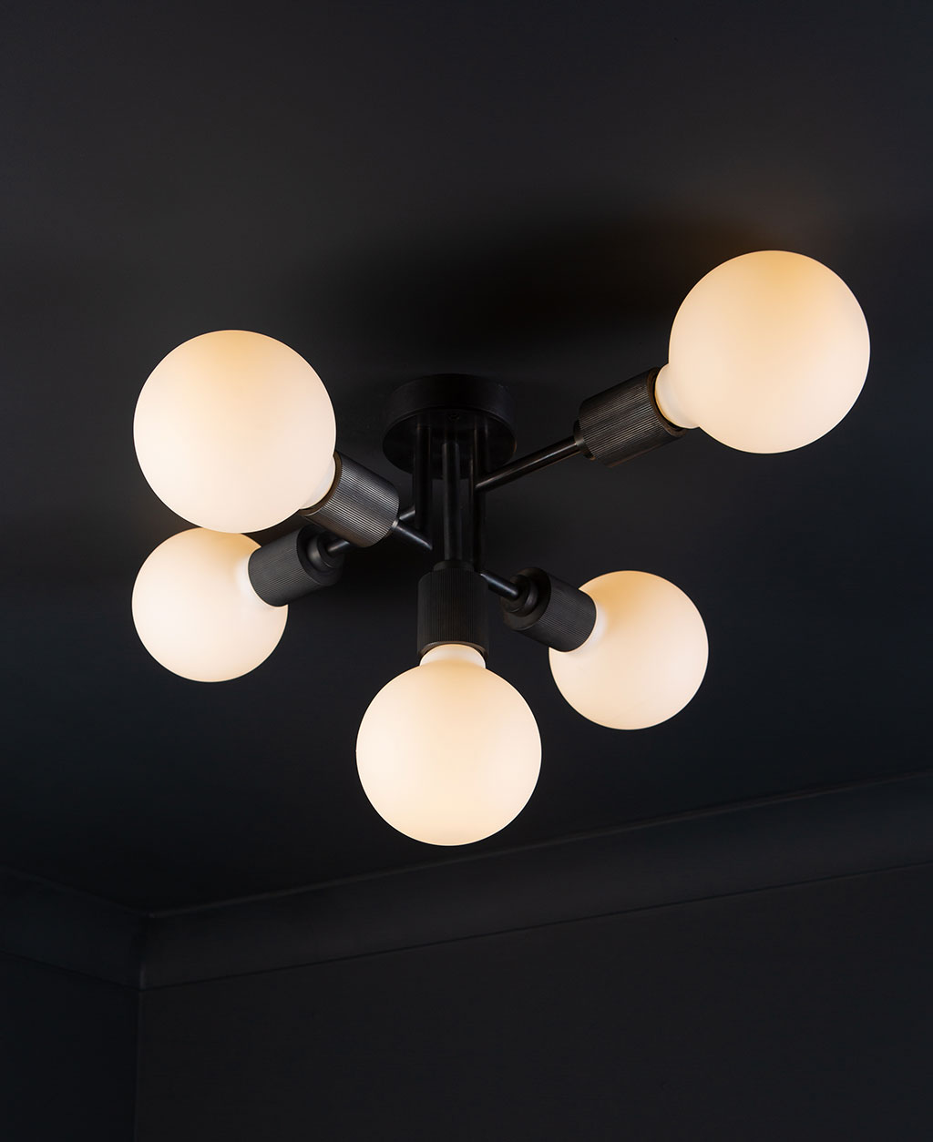 connaught black ceiling light with lit frosted bulbs against black ceiling