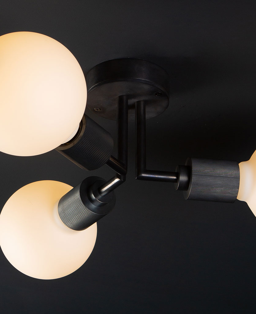 closeup hoxton antique black ceiling light with 3 lit bulbs on black ceiling