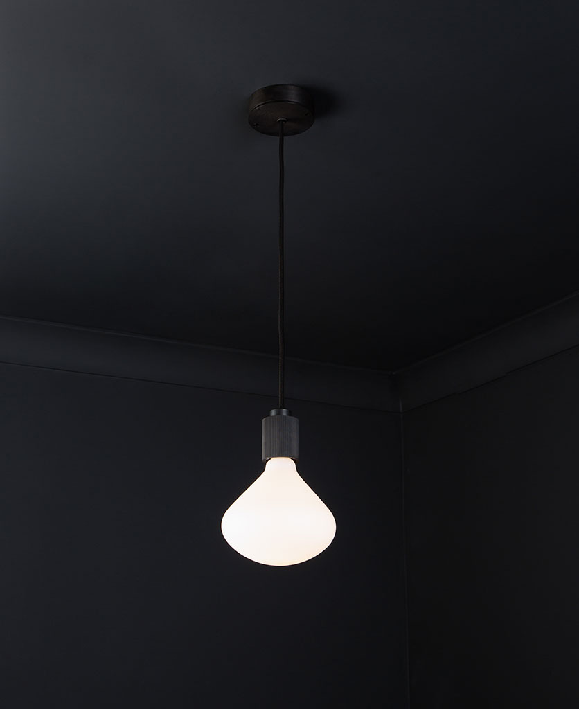 antique black lanesborough pendant ceiling light suspended from an antique black ceiling rose with black fabric cable and opal light bulb against a black wall
