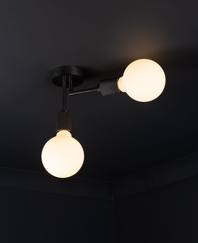 Langham LED flush ceiling lights antique black two arm light with 2 lit bulbs against a black background