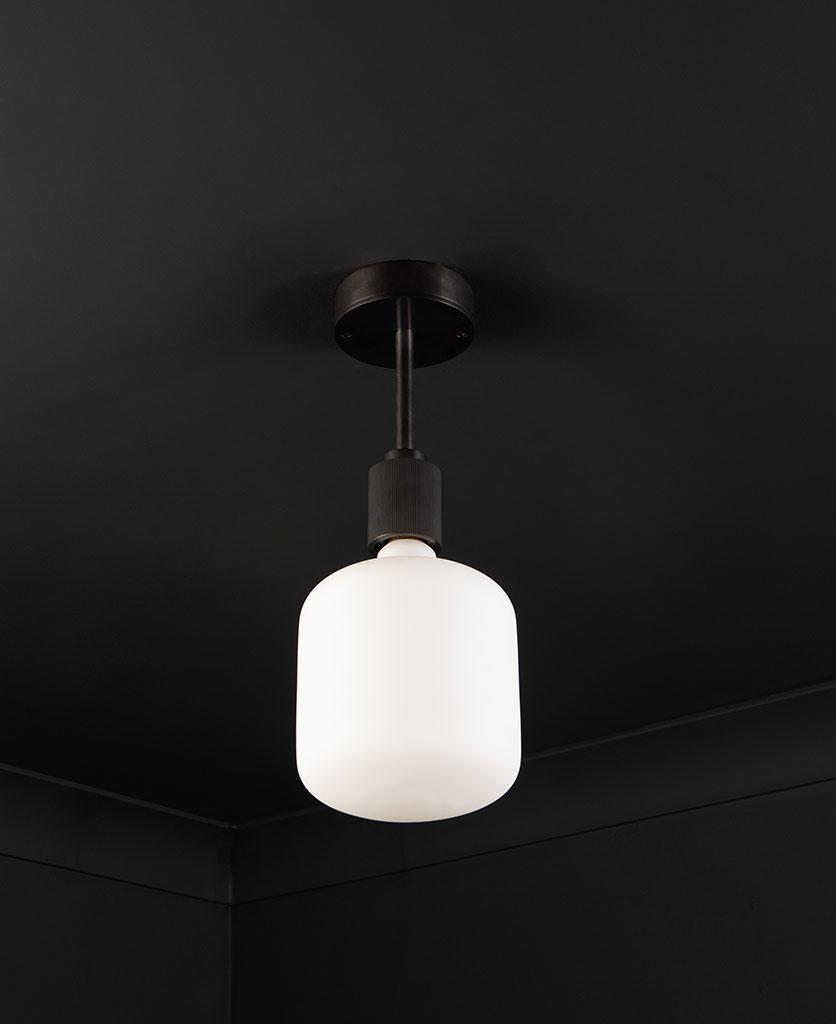 antique black Portobello flush mount ceiling light with unlit light bulb on black ceiling