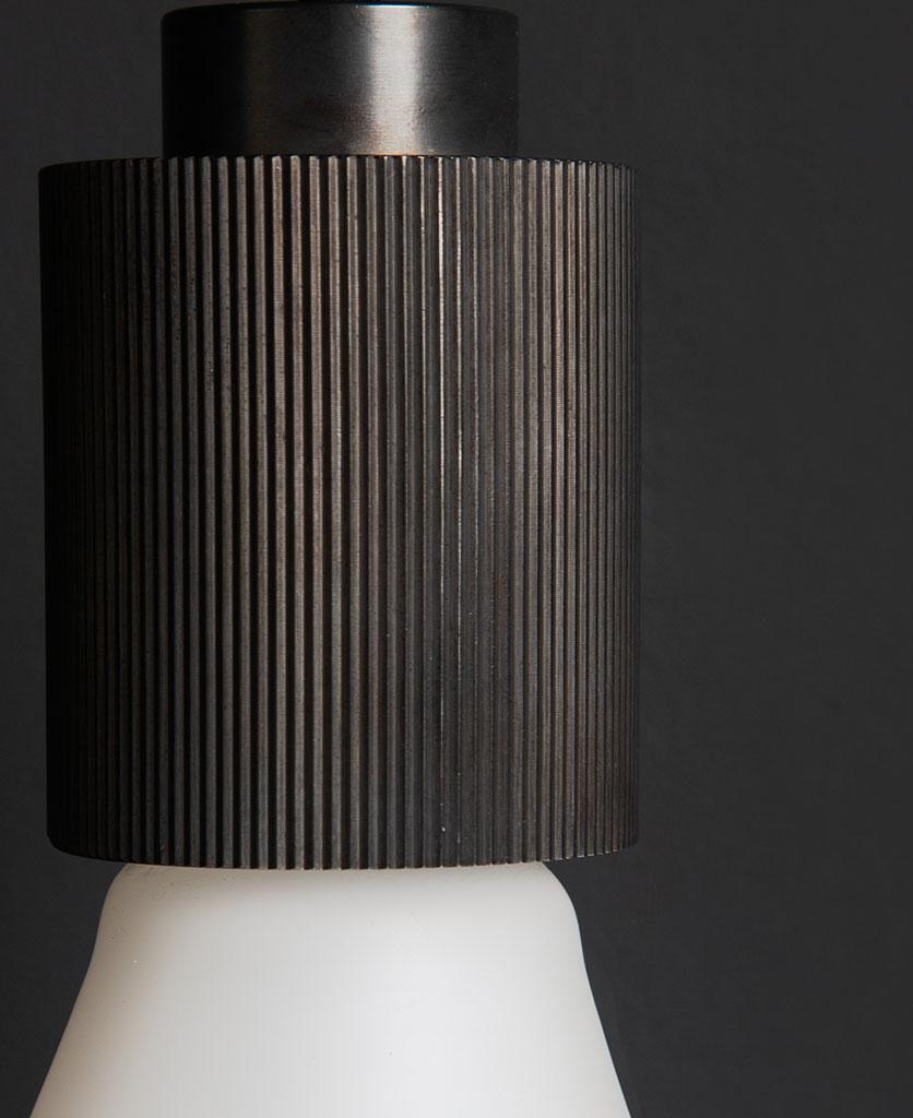 antique black ribbed bulb holder against black wall