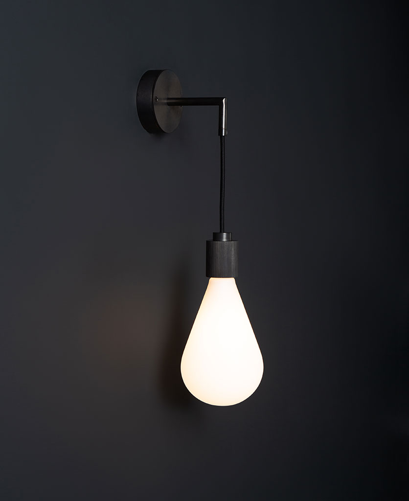ritz antique black wall light fittings with lit bulb against black background